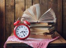 Despertador retro vermelho e uma pilha de livros na tabela Fotografia de Stock
