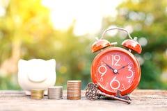 Despertador rojo con la moneda en la madera vieja fotos de archivo libres de regalías