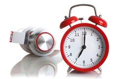 Despertador rojo con los auriculares aislados Fotos de archivo libres de regalías