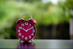 Despertador rojo del metal del reloj antiguo negro en día rojo del ` s de la tarjeta del día de San Valentín foto de archivo