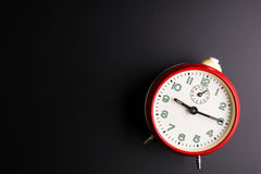 Despertador rojo en el fondo negro, concepto del tiempo, precipitación Imagenes de archivo