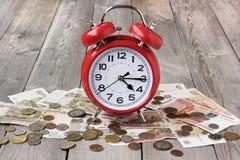 Despertador rojo y dinero ruso en la tabla de madera Fotos de archivo