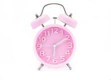 Despertador rosado en blanco fotos de archivo libres de regalías