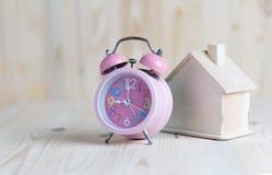 Despertador rosado y un lugar de la casa en la tabla y la madera de madera imagenes de archivo