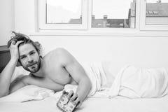 Despertador sin afeitar del control de la cama de la endecha del hombre Cara despierta barbuda sin afeitar del hombre que tiene h foto de archivo libre de regalías