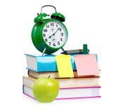 Despertador verde grande con los libros y la manzana Fotografía de archivo