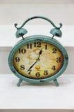 Despertador verde oval em um fundo de madeira Foto de Stock Royalty Free