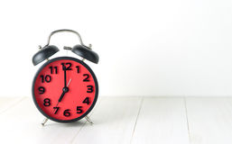 Despertador vermelho da manhã que aponta no 7:00 Fotografia de Stock Royalty Free