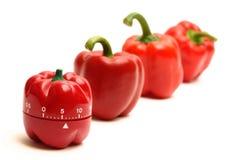 Despertador vermelho e pimentas vermelhas foto de stock royalty free