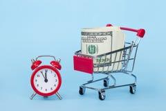 Despertador vermelho e um trole do supermercado com dólares em um fundo azul fotografia de stock royalty free