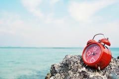Despertador vermelho no fundo da rocha e do mar Imagens de Stock Royalty Free