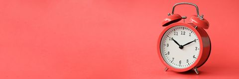Despertador viejo coralino en fondo rojo foto de archivo libre de regalías