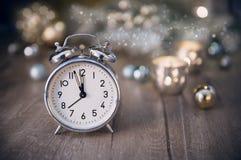 Despertador viejo que muestra cinco a la medianoche y al decorati que brilla Imagen de archivo
