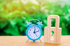Despertador y candado azules El concepto de una alarma o de una prohibición temporal, congelando Protección comprobada de la prot imagen de archivo libre de regalías
