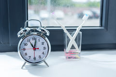Despertador y cepillos de dientes en vidrio en casa Imagen de archivo libre de regalías