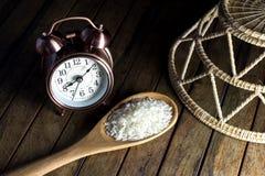 Despertador y cuchara y cesta viejos del arroz Foto de archivo libre de regalías