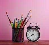Despertador y escuela inmóviles en cesta en rosa de madera de la tabla Imágenes de archivo libres de regalías