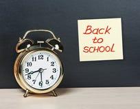 Despertador y etiqueta engomada con el texto de nuevo a escuela en el chalkboa Foto de archivo