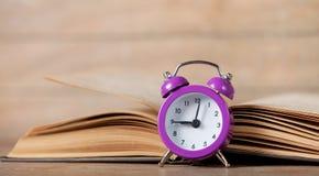 Despertador y libro Imagen de archivo libre de regalías