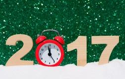 Despertador y los números 2017 en una nieve acumulada por la ventisca en un fondo del brillo Foto de archivo libre de regalías