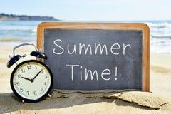 Despertador y pizarra con el tiempo de verano del texto Foto de archivo libre de regalías