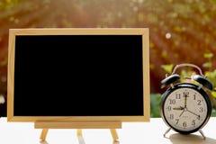 Despertador y pizarra o pizarra en el parque público para su plan del tablero del texto con concepto del tiempo foto de archivo libre de regalías