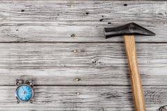 Despertador y un martillo en fondo de madera fotografía de archivo