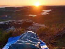 Despertar bonito em um saco-cama na borda da rocha Os pássaros estão cantando e Sun no horizonte Imagens de Stock Royalty Free