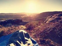 Despertar bonito em um saco-cama na borda da rocha Os pássaros estão cantando e Sun no horizonte Imagem de Stock