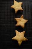 Despesas gerais de biscoitos dados forma de três estrelas do Natal na cremalheira refrigerando Imagens de Stock Royalty Free