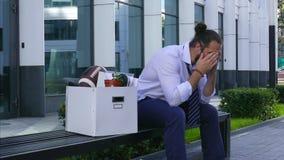 Despido y reclutamiento Un empleado trastornado se sienta en un banco en un centro de negocios con una caja del cortona y artícul almacen de video