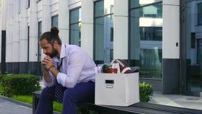 Despido y reclutamiento Un empleado trastornado se sienta en un banco en un centro de negocios con una caja del cortona y artícul metrajes
