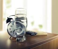 Despierte con el reloj de alarma y un vidrio de agua imágenes de archivo libres de regalías