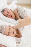 Despierte a la mujer mayor en la cubierta de cama sus oídos Imágenes de archivo libres de regalías
