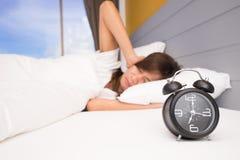 Despierte, mujer asiática en mano que extiende de la cama al despertador la muchacha apaga el despertador que despierta por la ma foto de archivo