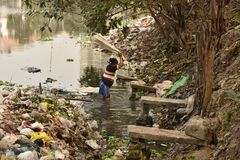 Dirty Laundry: Washerman wash clothes in polluted water royalty free stock image