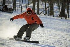 Desplazamiento del snowboarder en el flanco de la colina Imagen de archivo libre de regalías