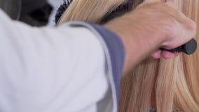 Desplazamiento del tiro de un pelo que hace el brushing del peluquero profesional de su cliente metrajes
