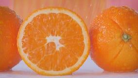 Desplazamiento a lo largo de las naranjas adonde el agua está rociando sobre ellas almacen de metraje de vídeo