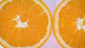 Desplazamiento a lo largo de rebanadas de las naranjas en un fondo blanco y mojado almacen de metraje de vídeo
