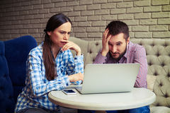 Despondent couple looking at laptop Royalty Free Stock Photography
