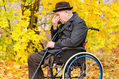 Despondent despairing senior amputee. Sitting wheelchair outdoors colourful yellow autumn park with head his hands holding crutches  hand Stock Photo