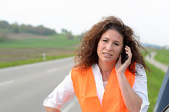 Despondent female driver trying to summon help. Despondent attractive young female driver trying to summon help on her mobile phone after breaking down at the stock images