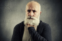 Despondent senior man over grey backround. Portrait of despondent senior man over grey backround stock photo