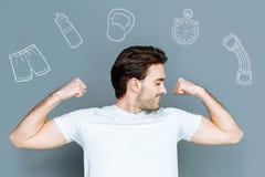 Desportista alegre que mostra seus músculos e que olha contente foto de stock