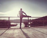 Desportista alto que aquece os músculos, esticando os pés antes da corrida fotografia de stock royalty free