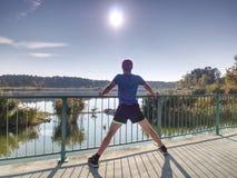 Desportista alto que aquece os músculos, esticando os pés antes da corrida imagens de stock