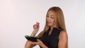 Desportista bonito que guarda uma bacia de salada, sorrindo à câmera filme
