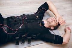 Desportista cansado que encontra-se no assoalho após a formação com ems imagem de stock royalty free