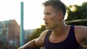 Desportista caucasiano considerável que relaxa após o exercício duro em barras paralelas fotografia de stock